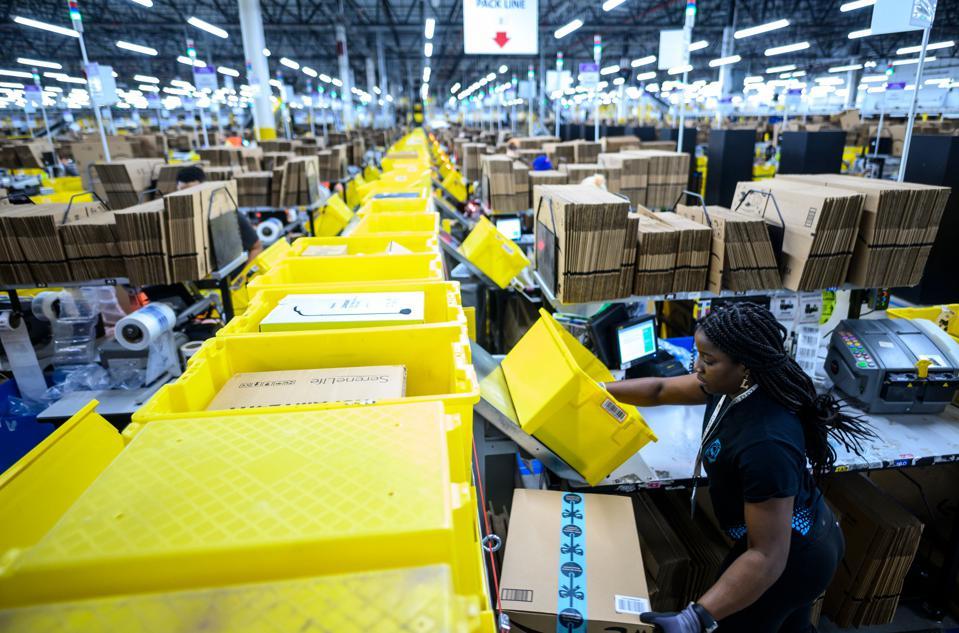 Bir kadın, bir Amazon lojistik merkezindeki paketleme istasyonunda çalışıyor.